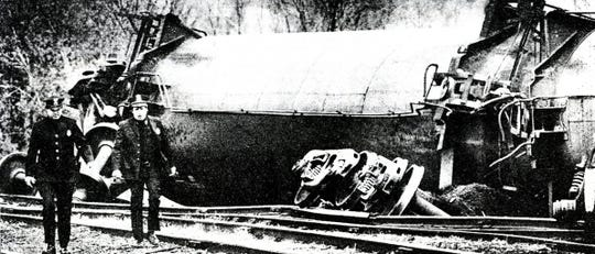 Patrolmen Tim Shores, left, and David Eggleston inspect the derailed train cars.