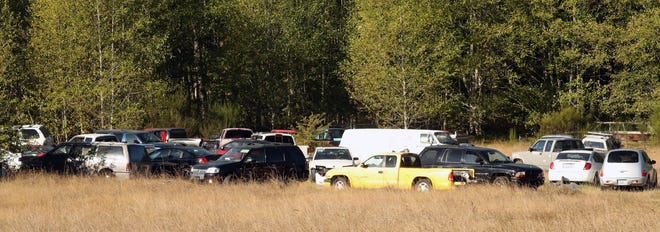 Vehicles parked in a field are visible from Big Valley Road in Poulsbo on Thursday. The state Court of Appeals in September upheld a ruling against the owner of the vehicles and the land by Kitsap County Superior Court.