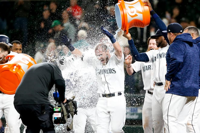 Mariners catcher Chris Herrmann gets a Gatorade shower after hitting a walk-off two-run home run against the Oakland Athletics during the 11th inning of Tuesday's 10-8 win.