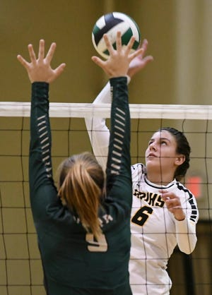 Lexy Denaburg of Merritt Island spikes past the block of Taylor Jensen of Viera during the Cape Coast Conference title match.