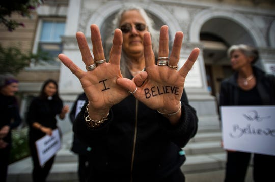 """Meg Kuhner of Montpelier shows her hands and the Sharpie words """"I Believe"""" during a protest outside City Hall in Montpelier, Vt., on Thursday, September 27, 2018, as the Senate Judiciary Committee heard testimony from Christine Blasey Ford and her accusations that Supreme Court nominee Brett Kavanaugh's sexual assaulted her as a teenager."""