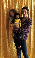 Melissa Fiorentino and her daughter, Stella, 4, stand in front of the gold curtain where girls can take party pictures at Stella & Toni.