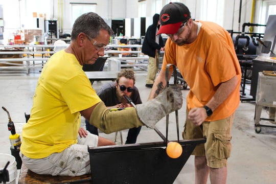 Joe Clabaugh, left, had dreamed of blowing glass for decades. But after seeing an ad for the seasonal Pumpkin Blows at Neusole Glassworks in Forest Park, he decided to give it a try. Here, he is seen in the early stages of shaping molten glass into what will eventually be a glass pumpkin.