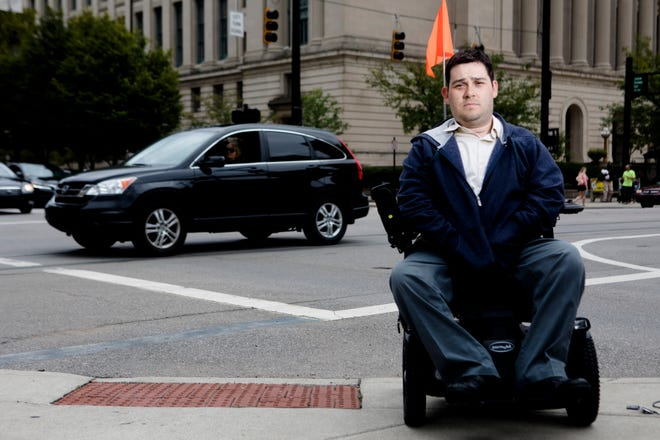 Neil Kelly sits in his wheelchair at an intersection on Sept. 11, 2018 in Downtown Cincinnati. Kelly has been struck by vehicles while in his wheel chair on three separate occasions.