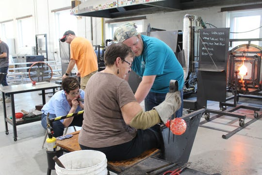 Cindy Garland, and author and retired educator from Springboro, works with a resident glassblower to shape a mass of molten glass into a glass pumpkin. She was attending one of the regular Pumpkin Blows at Neusole Glassworks in Forest Park.