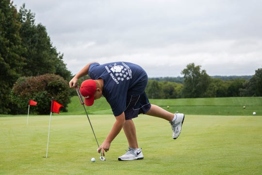 RJ Channon, deaf student athlete at East High School, picks up his golf balls while putting on the practice green on Tuesday, Sept. 23, 2018, at Bright Grandview Golf Course.