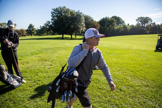 R.J. Channon, deaf student athlete at East High School, picks up his golf bag and walks to the next tee box while playing in a tournament on Wednesday at Bright Grandview Golf Course.