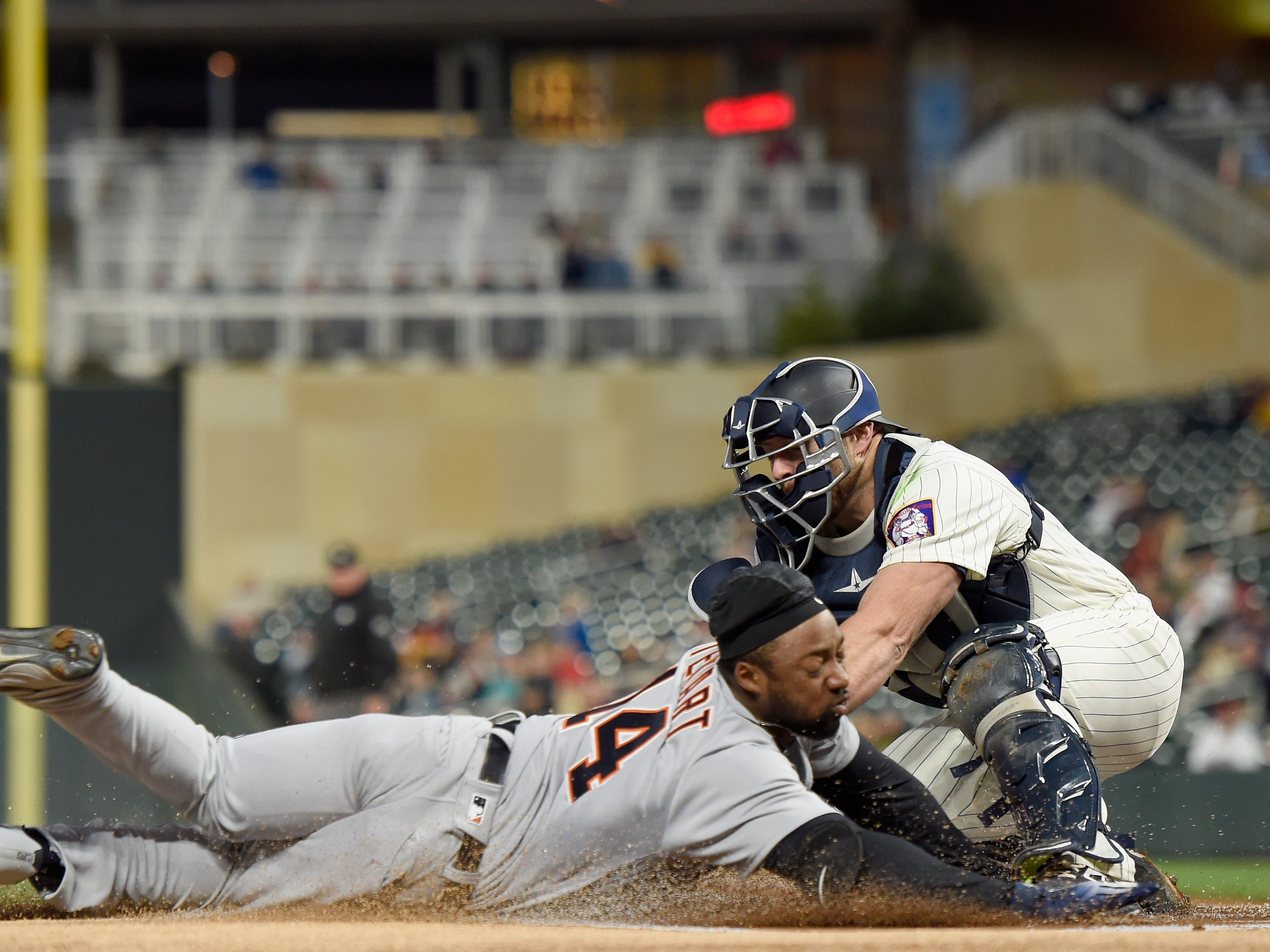 Chris Gimenez #46 of the Minnesota Twins tags out Christin Stewart #14 of the Detroit Tigers at home plate during the first inning of the game on September 26, 2018 at Target Field in Minneapolis, Minnesota.