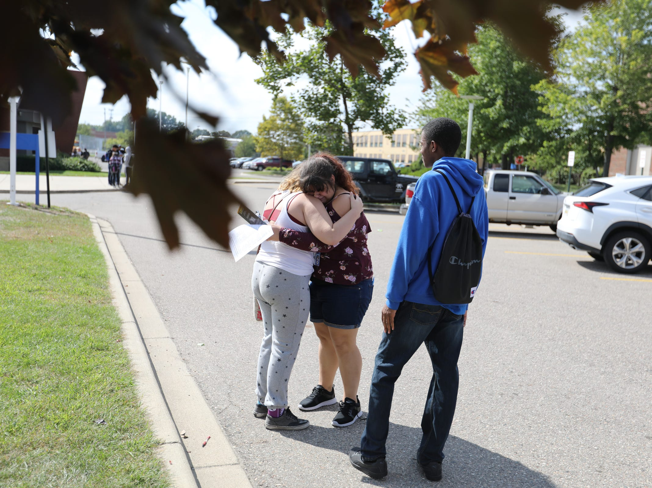 Victoria Oraczko, center, 16, of Warren is comforted by her friends after she was interviewed and released after the stabbing that occurred in her classroom at Fitzgerald High School in Warren, Mich. on Wednesday, Sept. 12, 2018
