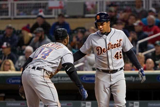 Detroit Tigers third baseman Jeimer Candelario (46) high fives outfielder Christin Stewart (14) after scoring on a triple by Stewart in the first inning against Minnesota Twins at Target Field on Sept. 26, 2018.