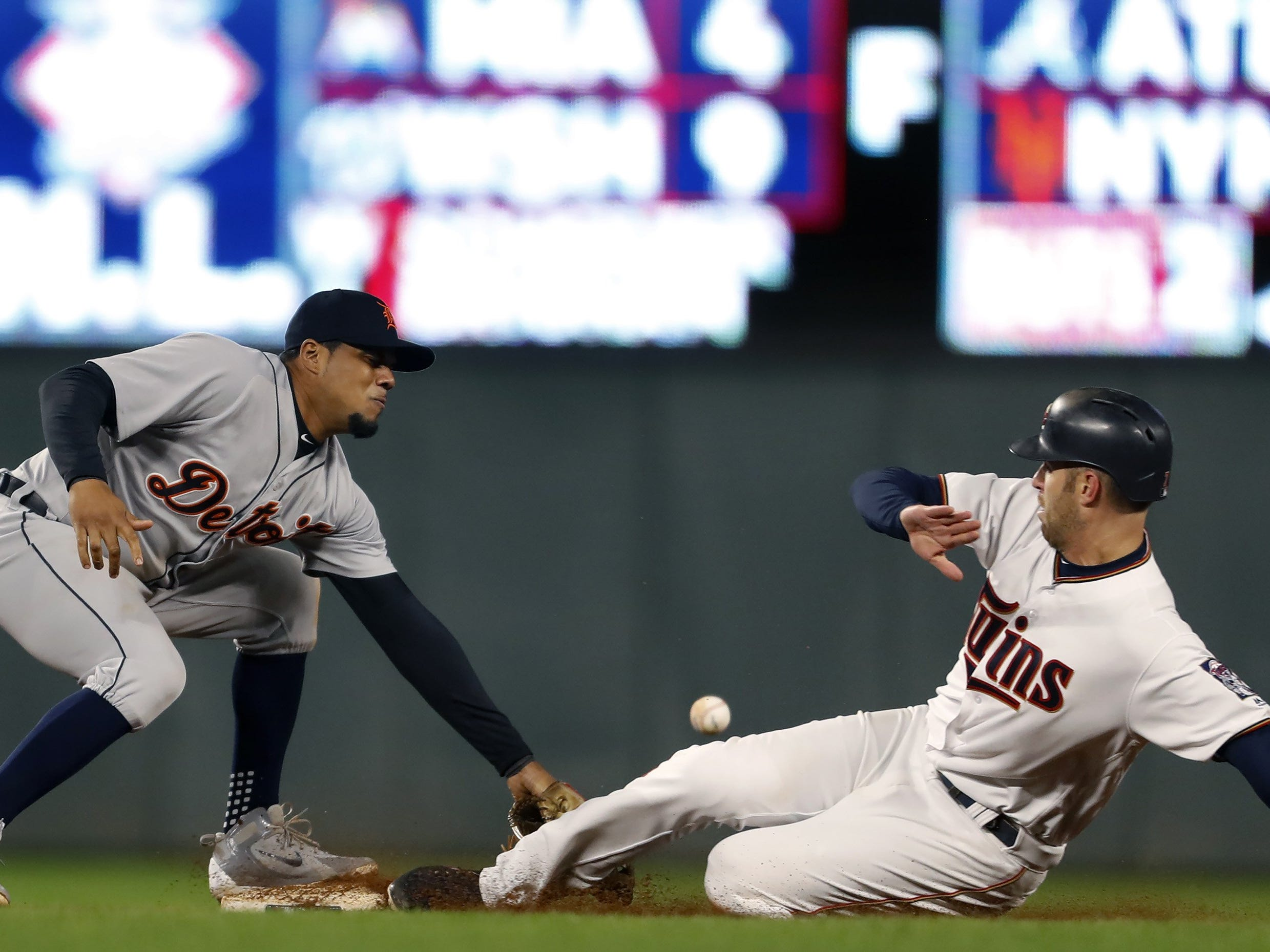 The Minnesota Twins' Joe Mauer, right, takes second base, then third base on a throwing error by Detroit Tigers catcher Joe McCann to infielder Jaime Candelario at Target Field in Minneapolis on Tuesday, Sept. 25, 2018. The Tigers won, 4-2.