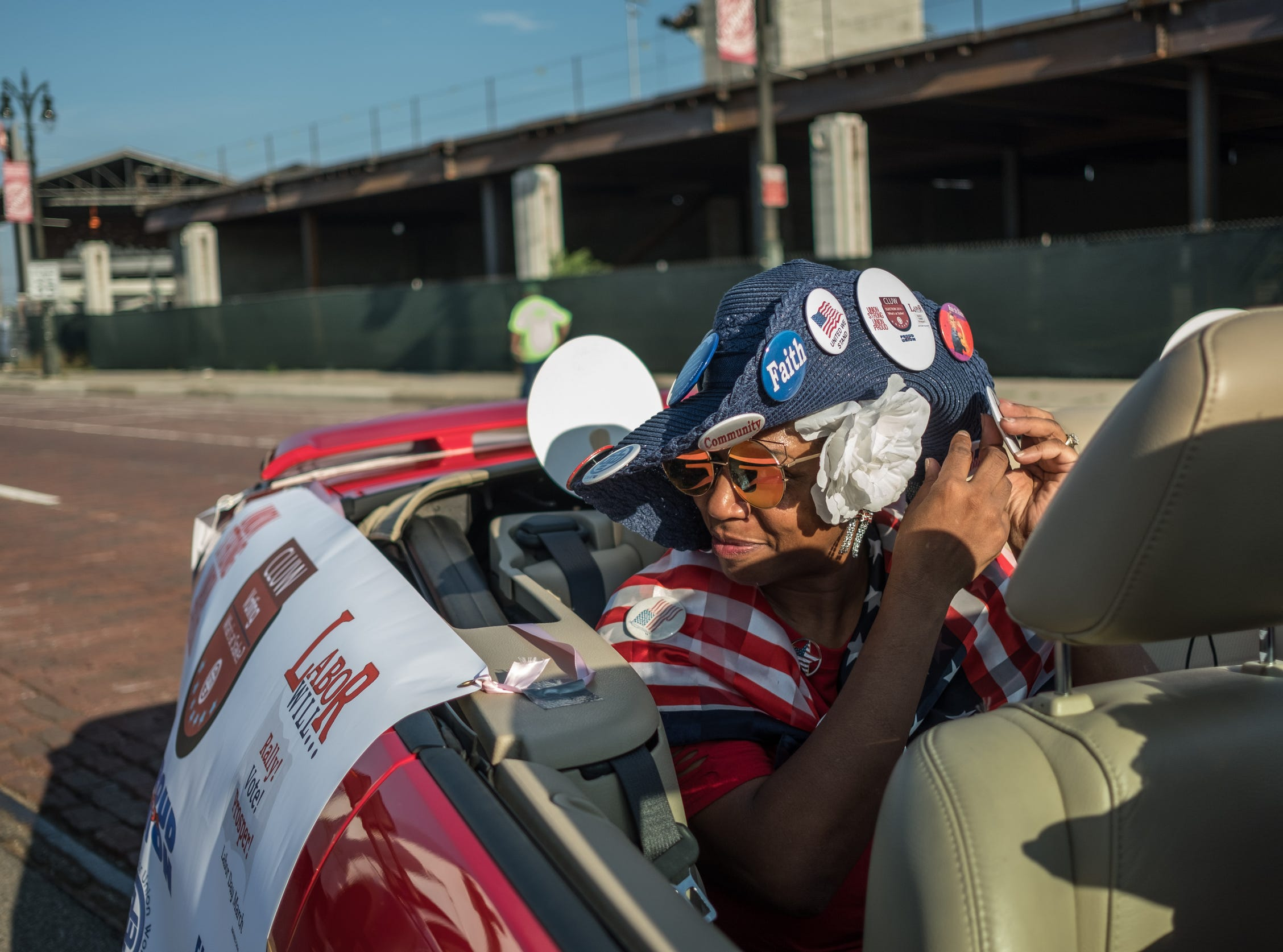 Coalition of Labor Union Women member Brenda Scott of Detroit fixes a butt on her hat while waiting to ride along in a convertible on Michigan Avenue in Corktown during Detroit's Labor Day Parade on Monday, September 3, 2018.