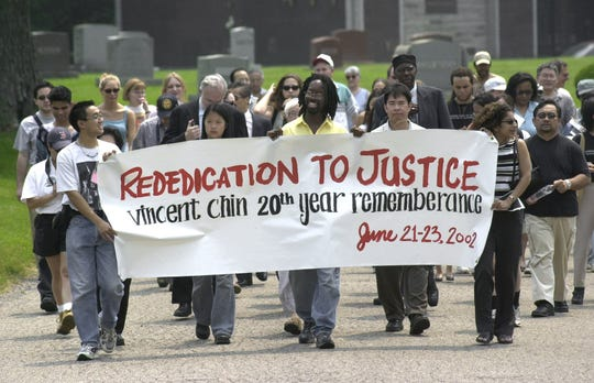 Activists walk to the grave of Vincent Chin during a 20th anniversary memorial for Chin at Forest Lawn Cemetery in Detroit on June 23, 2002.