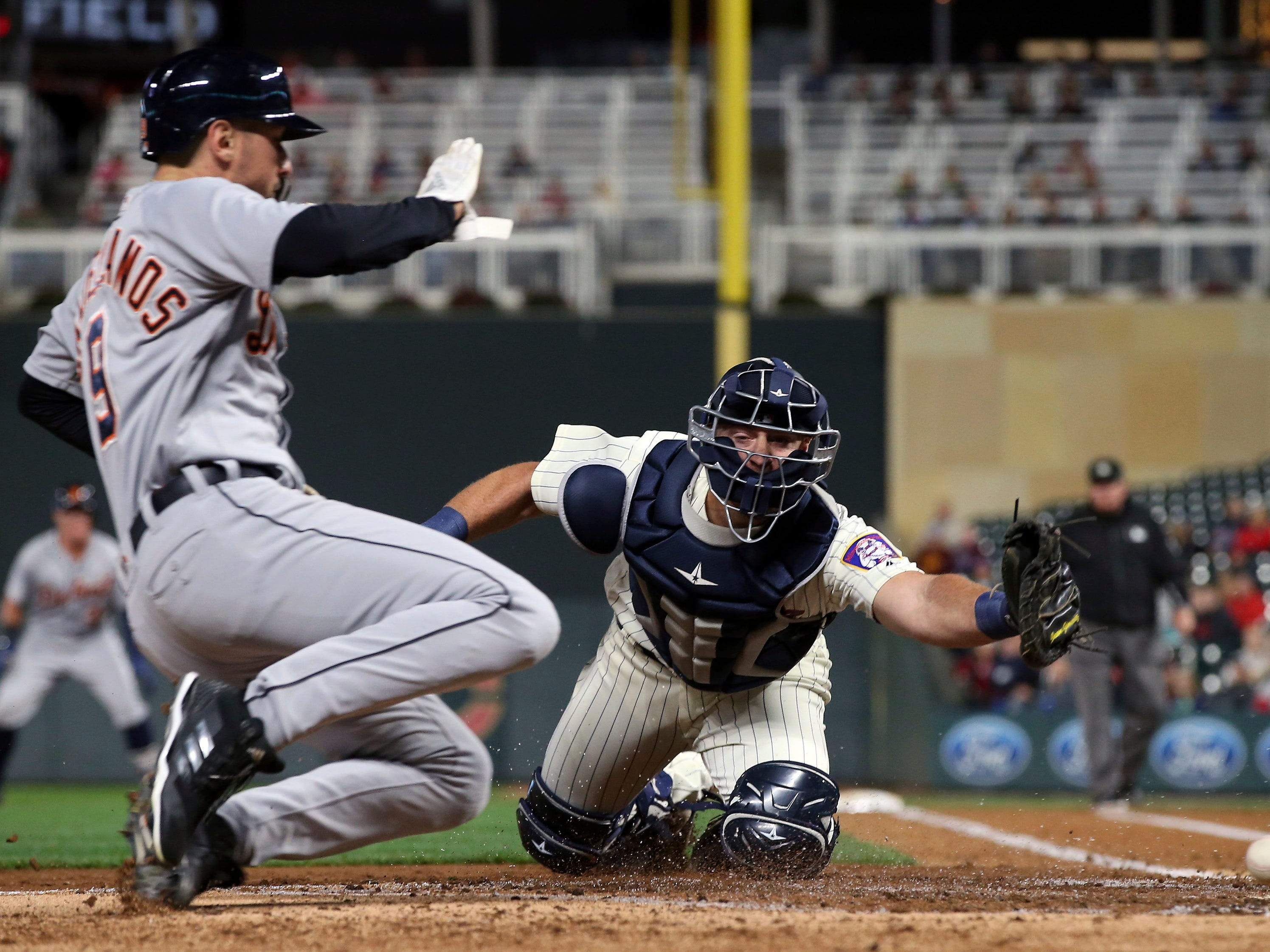 Minnesota Twins catcher Chris Gimenez, right, makes a futile reach for the throw as Detroit Tigers' Nicholas Castellanos slides in to score on a hit by James McCann during the third inning of a baseball game Wednesday, Sept. 26, 2018, in Minneapolis.