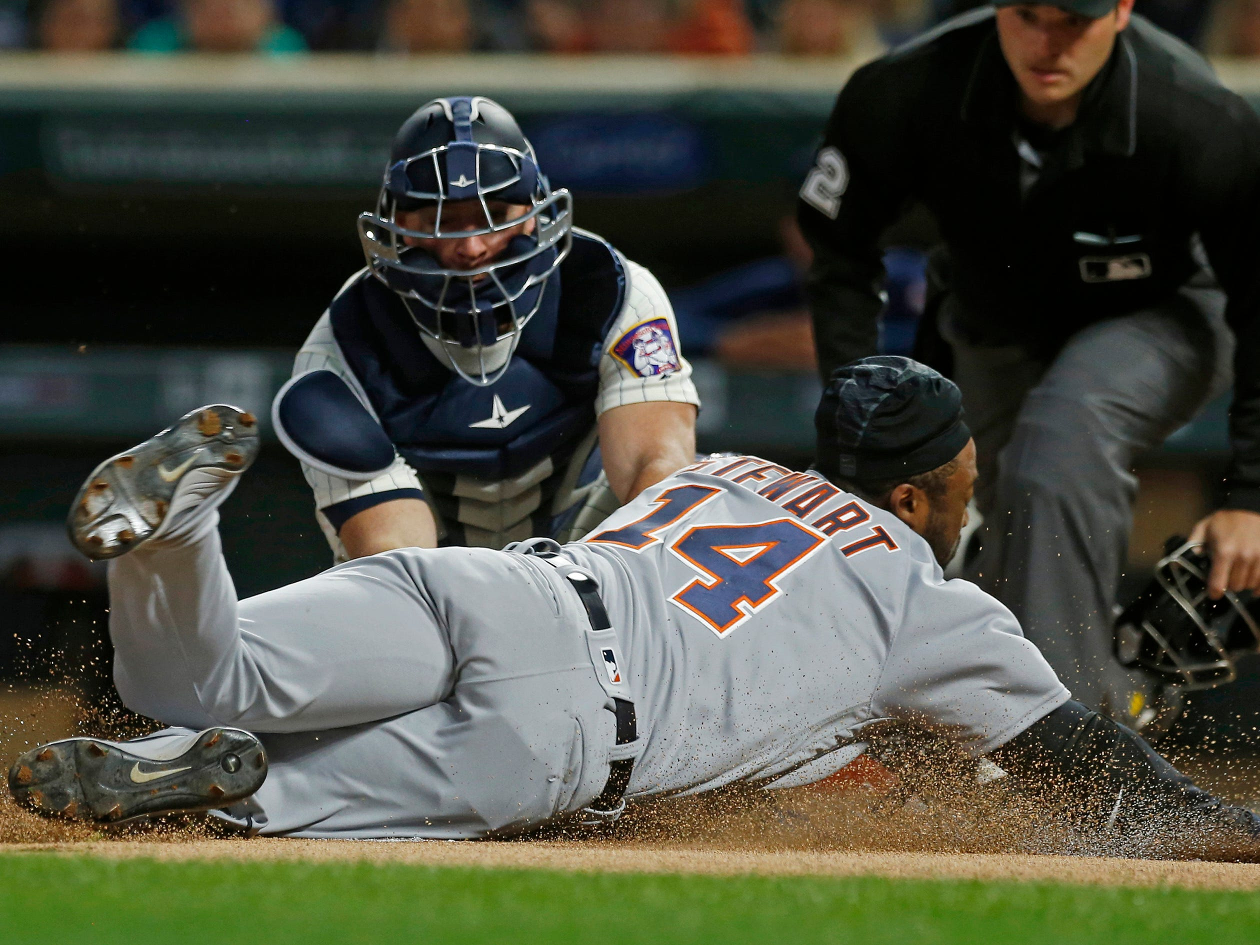 Minnesota Twins catcher Chris Gimenez, left, tags out Detroit Tigers' Christin Stewart as he attempted to score for an inside-the-park home run in the first inning of a baseball game Wednesday, Sept. 26, 2018, in Minneapolis.