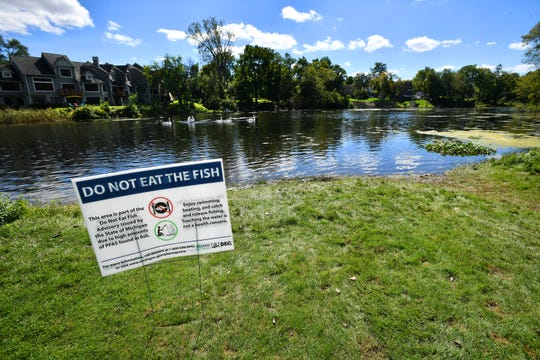 Signs warn boaters and fishermen of the dangers of eating fish from the Huron River at Central Park in Millford on Wednesday, Sept 26, 2018 .