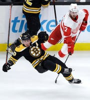 Boston Bruins left wing Brad Marchand, left, is upended by Detroit Red Wings defenseman Filip Hronek, right, during the third period of a preseason game.