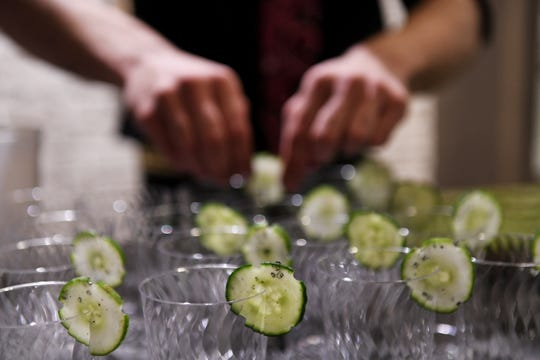 Bartender Yani Frye from Bad Luck in Detroit puts cucumber garnishes on sample cups for the cucumber envy smash he is makeing at the Dish and Design Kitchen Trends Event at EuroAmerica Design in Troy, Mich. on Sept. 26, 2018. (Robin Buckson / The Detroit News)