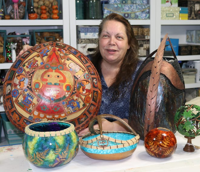 Gourd artist Chris Pawlik with a collection of her work.