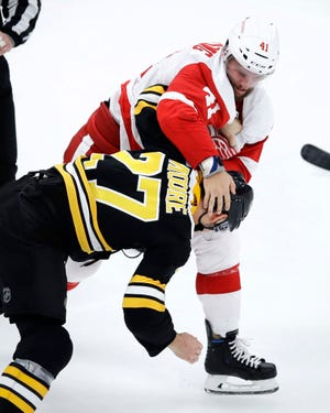 Detroit Red Wings center Luke Glendening wrestles Boston Bruins defenseman John Moore to the ice as they fight during the third period.