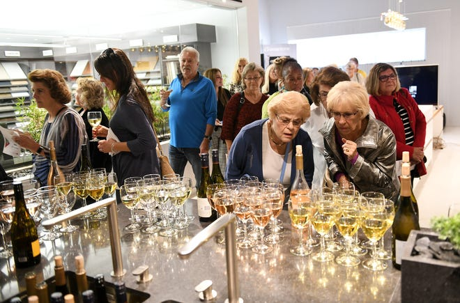 From right, Bernie Gibbons of Farmington Hills and Marie McLean of West Bloomfield look over the wine selection at the Dish and Design Kitchen Trends Event at EuroAmerica Design in Troy, Mich. on Sept. 26, 2018.