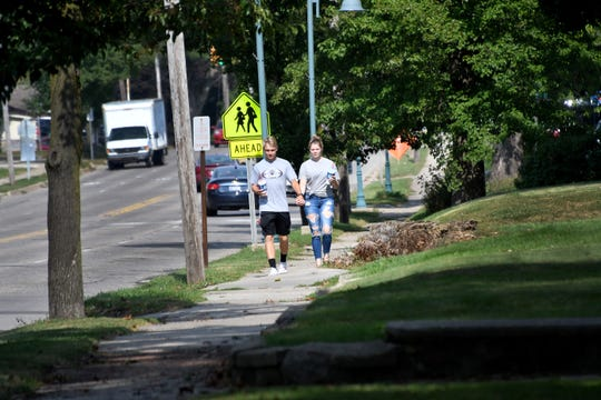 Two people walk in a neighborhood in Parchment. The city's water system was among 1,841 the state is testing for PFAS compounds.