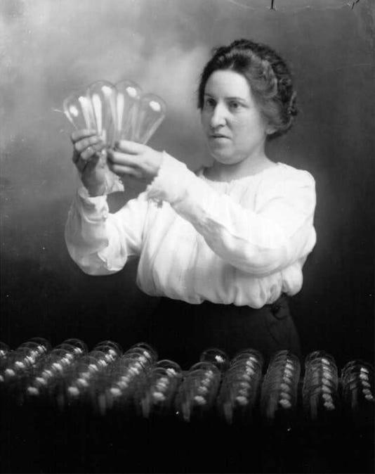 Woman Inspecting Lightbulbs