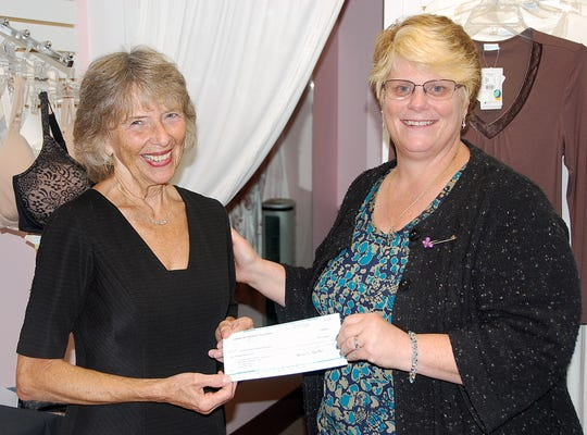 Lori Ann Congdon, right, of Corning Environmental Technologies, presents a $1,000 check from the Corning Foundation to Harolyn Giordano, program director of the YWCA Pink Boutique.