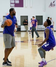 First-year University of Evansville men's basketball head coach Walter McCarty, left, is defended by Jawaun Newton during the first official practice of the year at the University of Evansville's Carson Center Thursday morning.