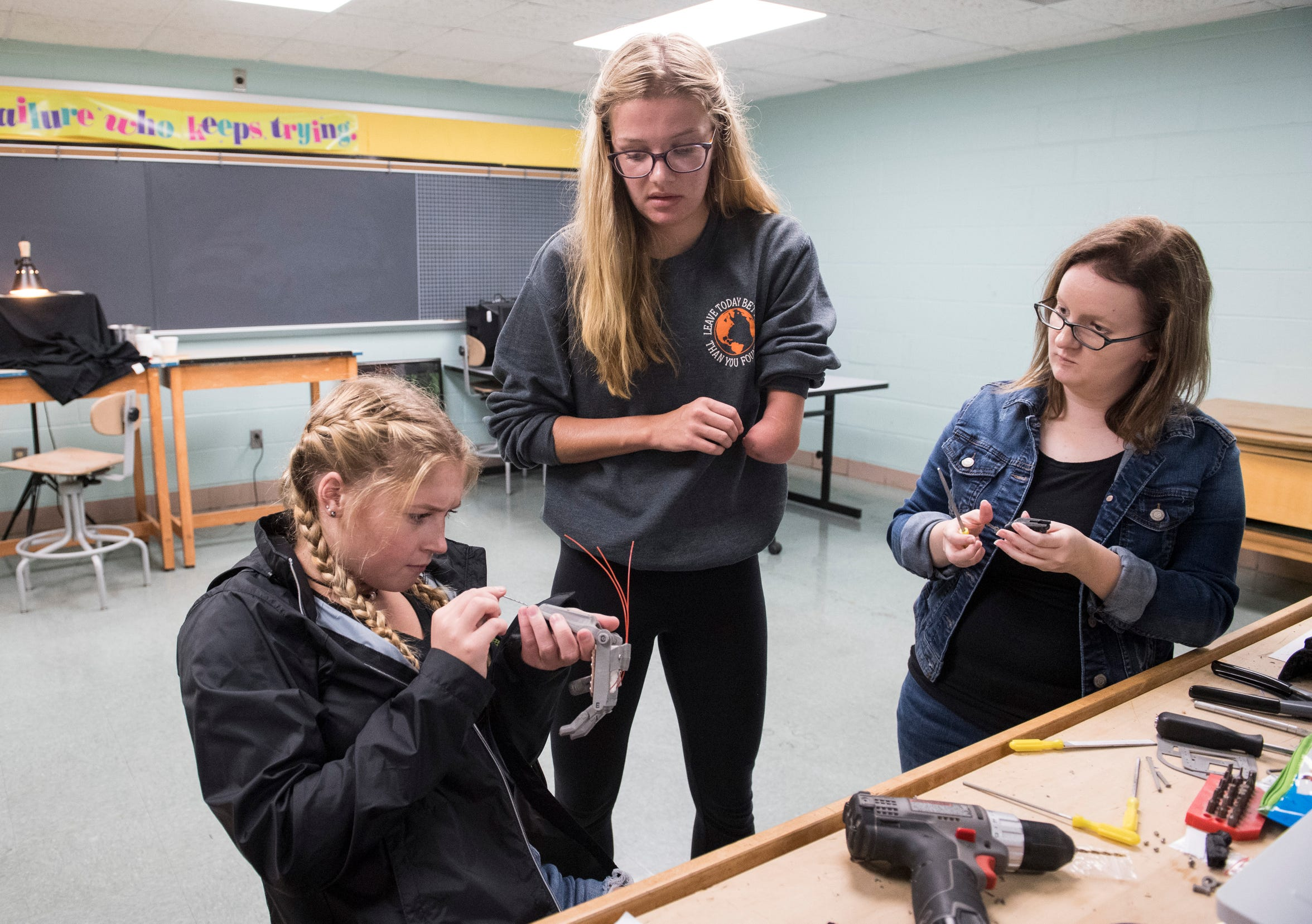 Kenzie Paul, middle, and classmates Erica Gerald, left, and Hanna Kiger, right, work on their ODY Hand, a 3D printable upper limb assistive device, during her Visual Communication class at Mt. Vernon high school Sept. 25, 2018.