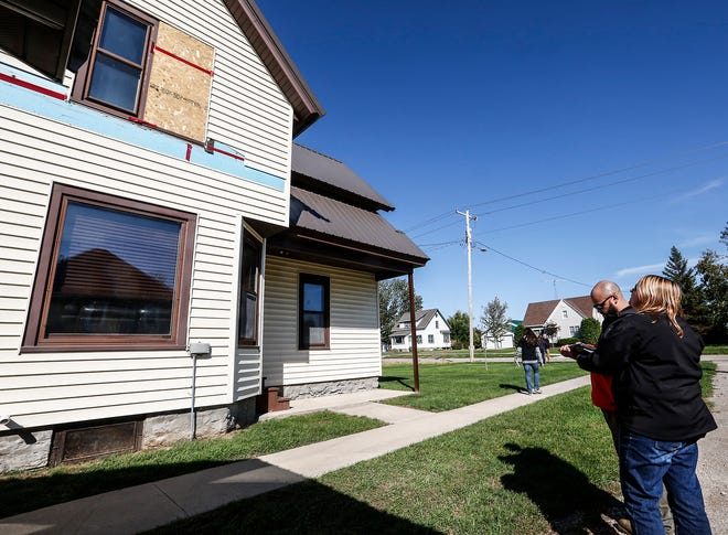 David Laboy of the Federal Emergency Management Agency and Jessica Hoffman of Wisconsin Emergency Management look at storm damage to a house Wednesday in Alto. Several FEMA groups toured the state to assess damage done by storms that spawned 19 tornadoes in Wisconsin on Aug. 28.