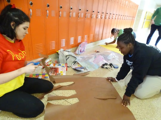 Fremont Ross juniors Kiley McCann, left, and Monique Smith work on homecoming decorations Thursday at the high school.