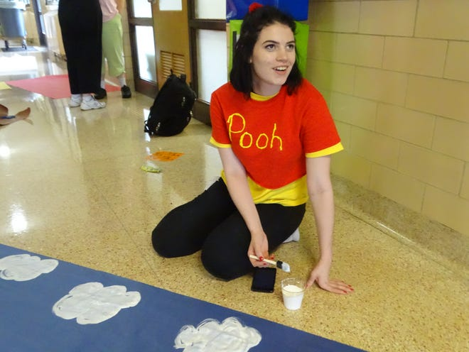 Fremont Ross High School junior Kiley McCann helps decorate the hallways Thursday afternoon as part of the school's homecoming activities. Fremont Ross will hold a pep rally Friday, with the football team hosting Lima Senior High School.