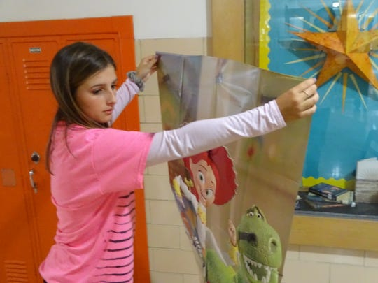 """Fremont Ross High School junior Lillie Swinehart holds up a """"Toy Story""""-themed decoration Thursday in a school hallway. Swinehart and dozens of other students helped decorate the school as part of homecoming week."""