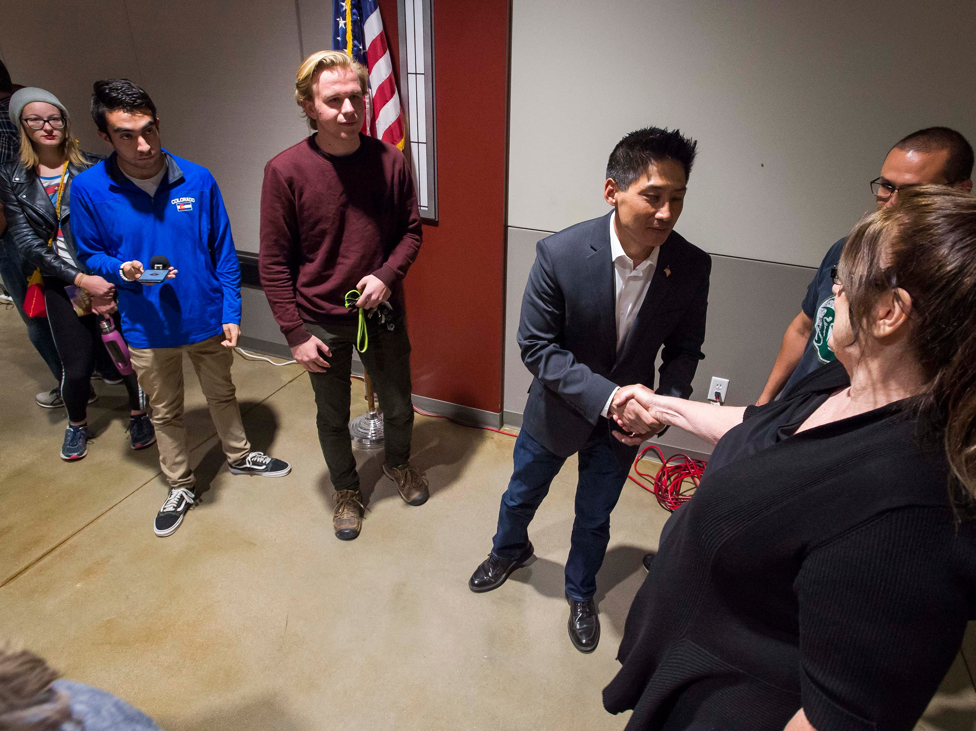 Colorado's 2nd Congressional District Republican Peter Yu shakes hands with St. Louis, Mo. resident Anna Stover after participated in a debate with Democratic nominee Joe Neguse on Wednesday, Sept. 26, 2018, at the Loveland Classical Schools in Loveland, Colo. Stover was in town visiting relatives.