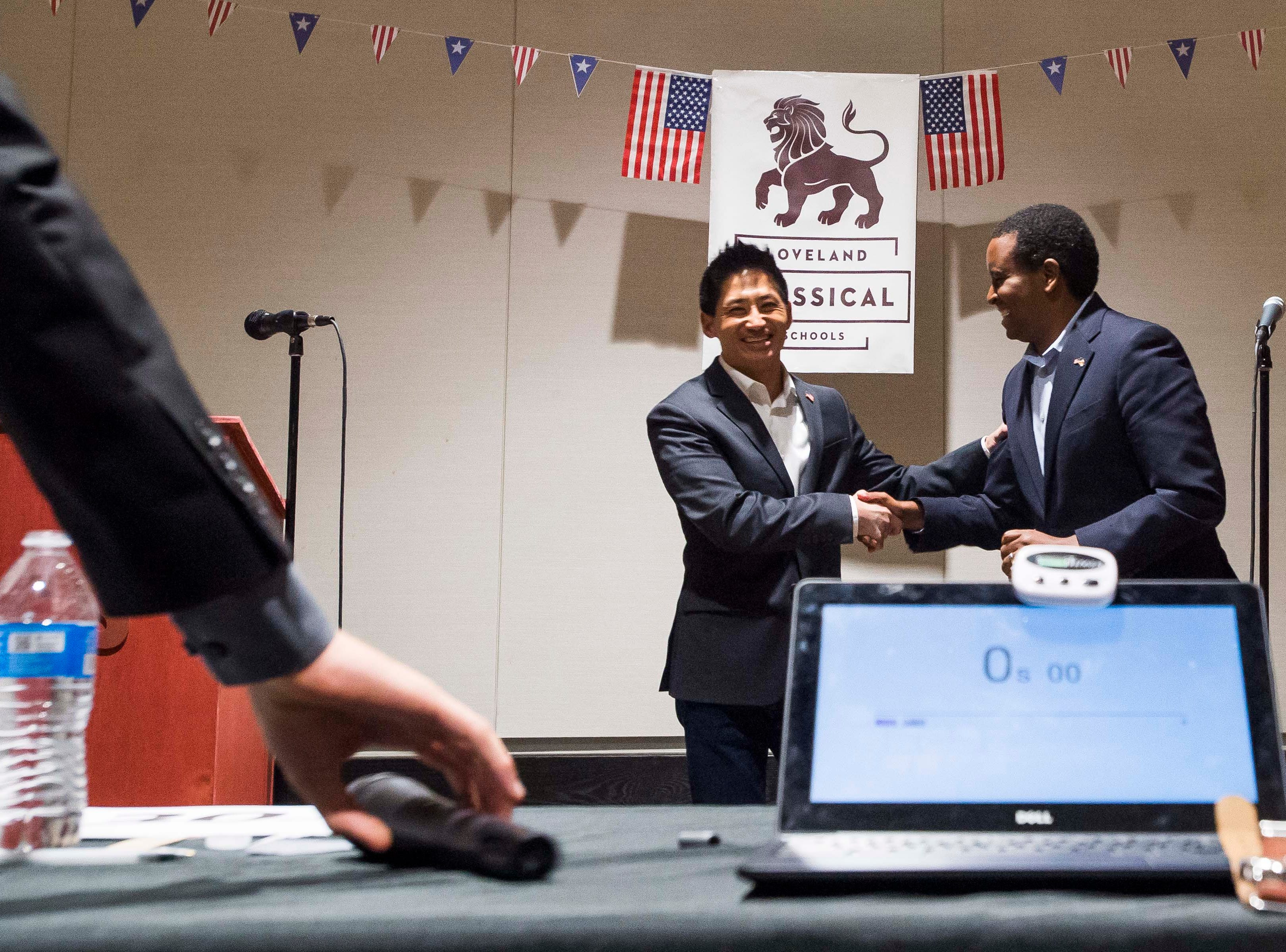Colorado's 2nd Congressional District Republican nominee Peter Yu, left, and Democratic nominee Joe Neguse, right, shake hands while moderator Tobias Hild grabs the microphone after a debate on Wednesday, Sept. 26, 2018, at the Loveland Classical Schools in Loveland, Colo.