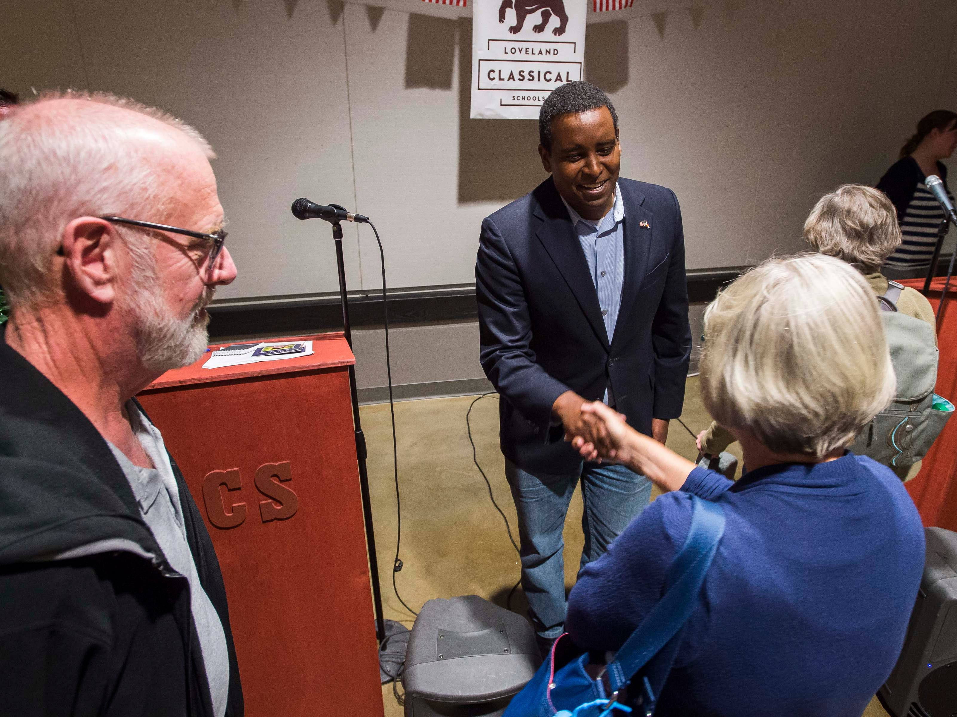 Colorado's 2nd Congressional District Democratic nominee Joe Neguse shakes hands with Loveland resident Becky Peters while her husband Tim looks on after Neguse participated in a debate with Republican nominee Peter Y on Wednesday, Sept. 26, 2018, at the Loveland Classical Schools in Loveland, Colo.