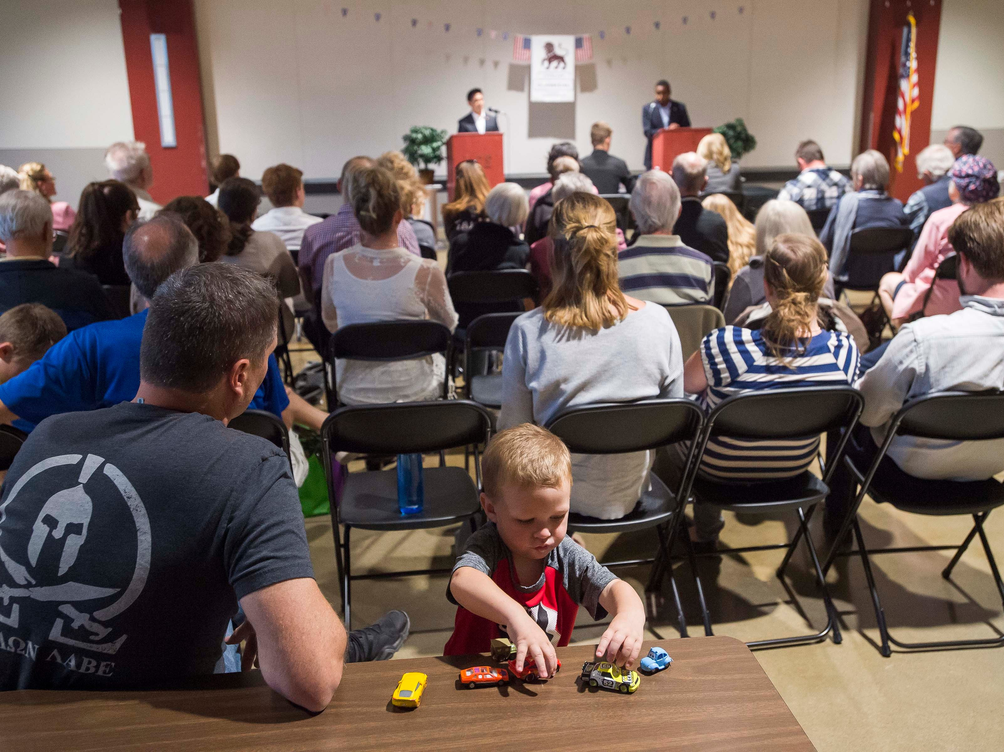 Beckham Coberly, 1, plays with toy cars while his father Guy Coberly watches a debate between Colorado's 2nd Congressional District Democratic nominee Joe Neguse and Republican nominee Peter Yu on Wednesday, Sept. 26, 2018, at the Loveland Classical Schools in Loveland, Colo.