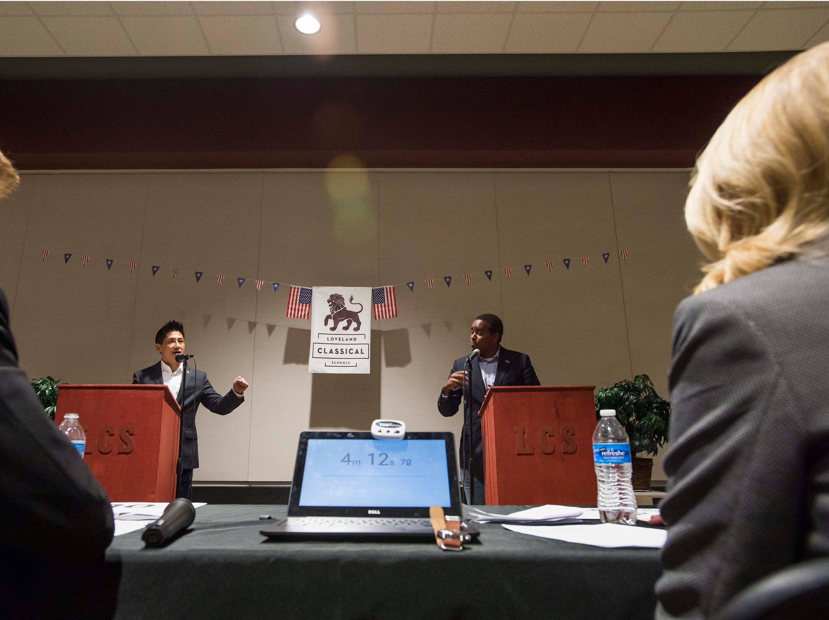 Colorado's 2nd Congressional District Republican nominee Peter Yu, center-left, and Democratic nominee Joe Neguse, center-right, cross-examine each other while moderators, Tobias Hild, left, and Zipporah Rowe, right, keep an eye on the timer on Wednesday, Sept. 26, 2018, at the Loveland Classical Schools in Loveland, Colo.
