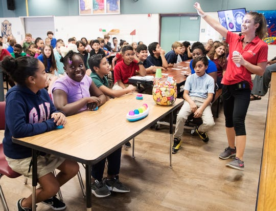 Danielle Zakett, the Healthy Living Lab Manager for the Lee County School District asks questions in Jeopardy game format to students from left, Aryana Polanco,10, left, Samantha Jean-Marie, 10,and Isaias Alvarado, 11, at Mirror Lake Elementary School on Thursday 9/27/2018.