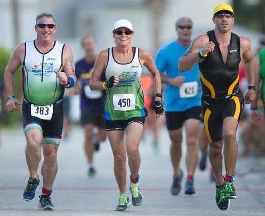 Hundreds of athletes compete recently in the Galloway Captiva Triathlon in Captiva, Florida. The recent red tide outbreak forced race organizers to replace the swim portion with a quarter mile run on the beach.