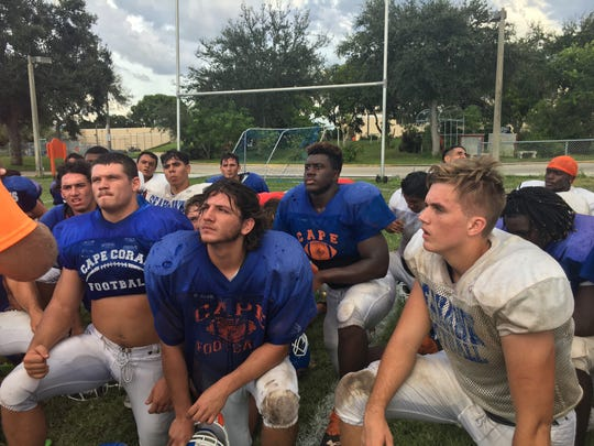 Tre'shaun Clark (center, second row) listens with Cape Coral teammates to coaches' instructions after practice Aug. 26, 2018.