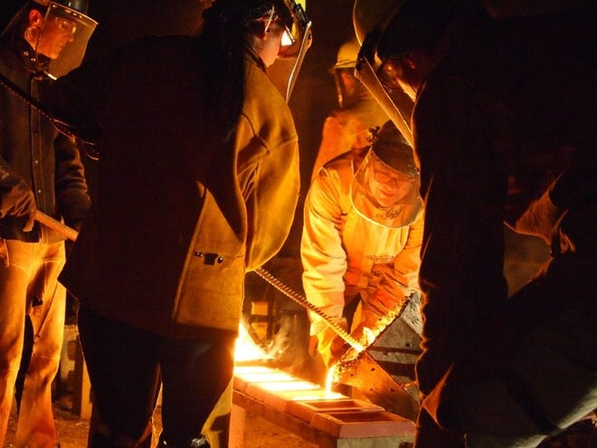 Peninsula School of Art Executive Director Catherine Hoke helps pour molten iron into the molds to create artistic iron tiles at last year's Community Iron Pour.