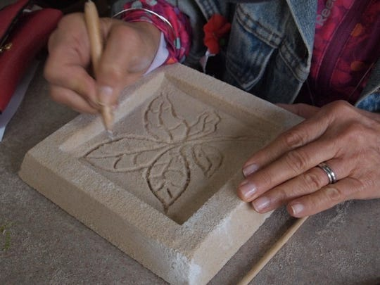 Guests at Peninsula School of Art's Community Iron Pour use simple tools to scratch a design into a preformed mold.