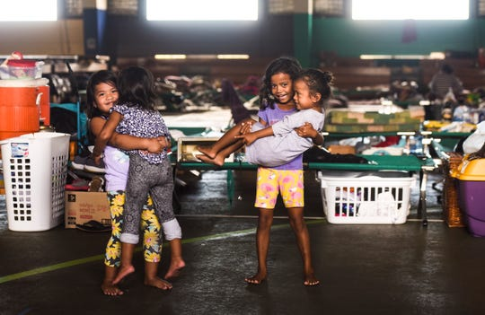 Young children past the time away as they play amongst sleeping cots and personal items of those who have sought temporary shelter at the Astumbo gym in Dededo on Thursday, Sept. 27, 2018.