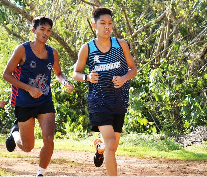 Brandon Miranda, at center, is the PDN's Player of the Week. The cross country runner for St. Paul stayed undefeated after 7 meets, even after challenging Okkodo Bulldogs Kyle Delos Santos (shown at left) who was also undefeated coming into the match.