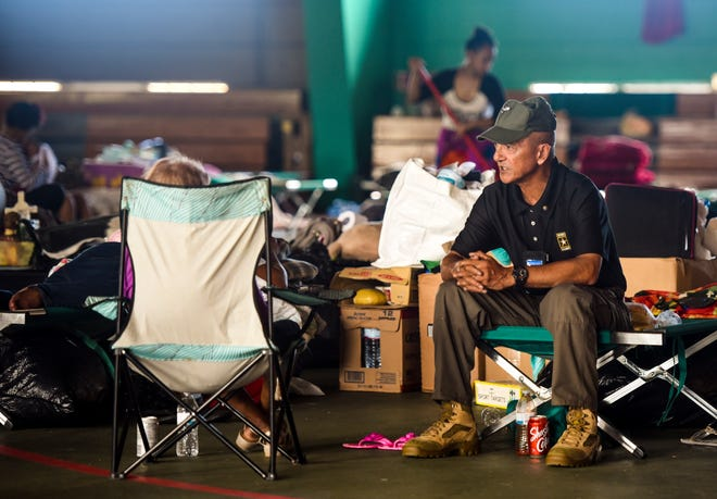 Anthony Lukeala, Guam Homeland Security shelter operation employee, chats with a resident staying at the temporary shelter still opened at the Astumbo gym in Dededo on Thursday, Sept. 27, 2018.