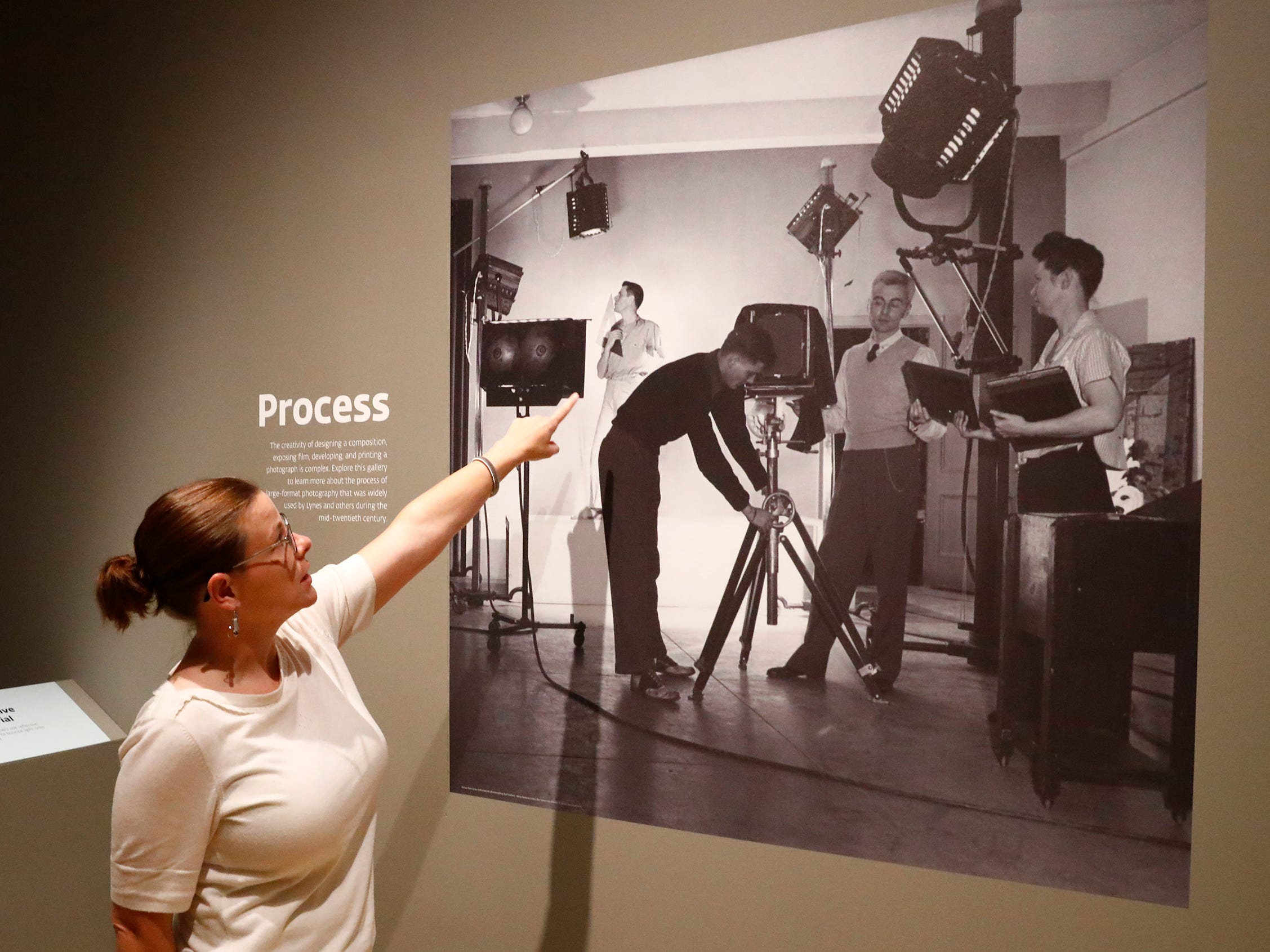 "Anne Young, one of the three curators of the ""Sensual / Sexual / Social:  The Photography of George Platt Lynes"" exhibit at Newfields, shows a photo, Wednesday, Sept. 26, 2018, of Lynes, center working in his studio. Lynes gained fame as a commercial and ballet photographer in the 1930s and 1940s, but he wanted to be known for the male nudes he captured of the male ballet dancers and others.  The exhibit runs Sept. 30, 2018 through Feb. 24, 2019."