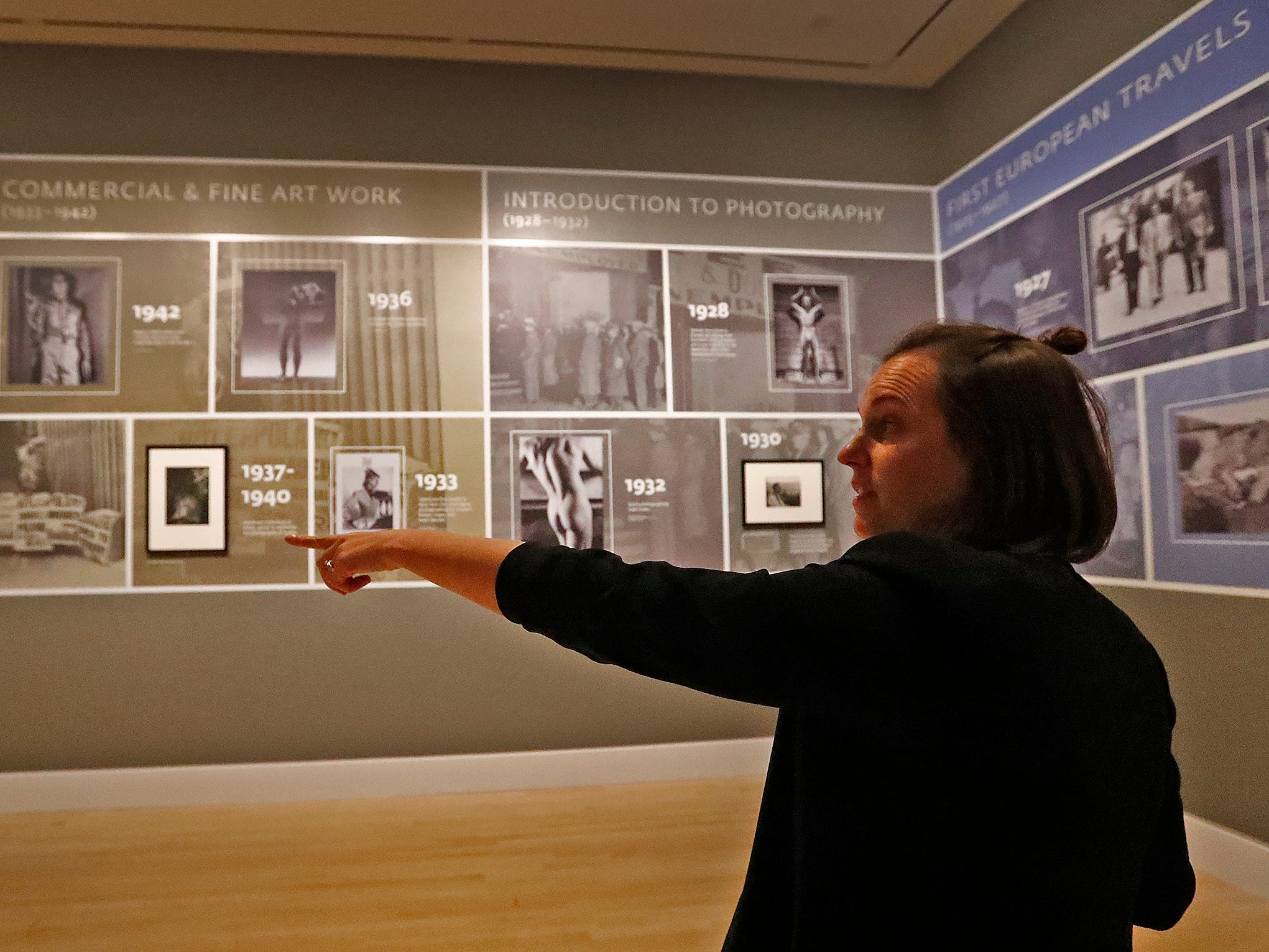 "Robin Lawrence, one of the three curators of the ""Sensual / Sexual / Social:  The Photography of George Platt Lynes"" exhibit at Newfields, shows a timeline of his work, Wednesday, Sept. 26, 2018. Lynes gained fame as a commercial and ballet photographer in the 1930s and 1940s, but he wanted to be known for the male nudes he captured of the male ballet dancers and others.  The exhibit runs Sept. 30, 2018 through Feb. 24, 2019."