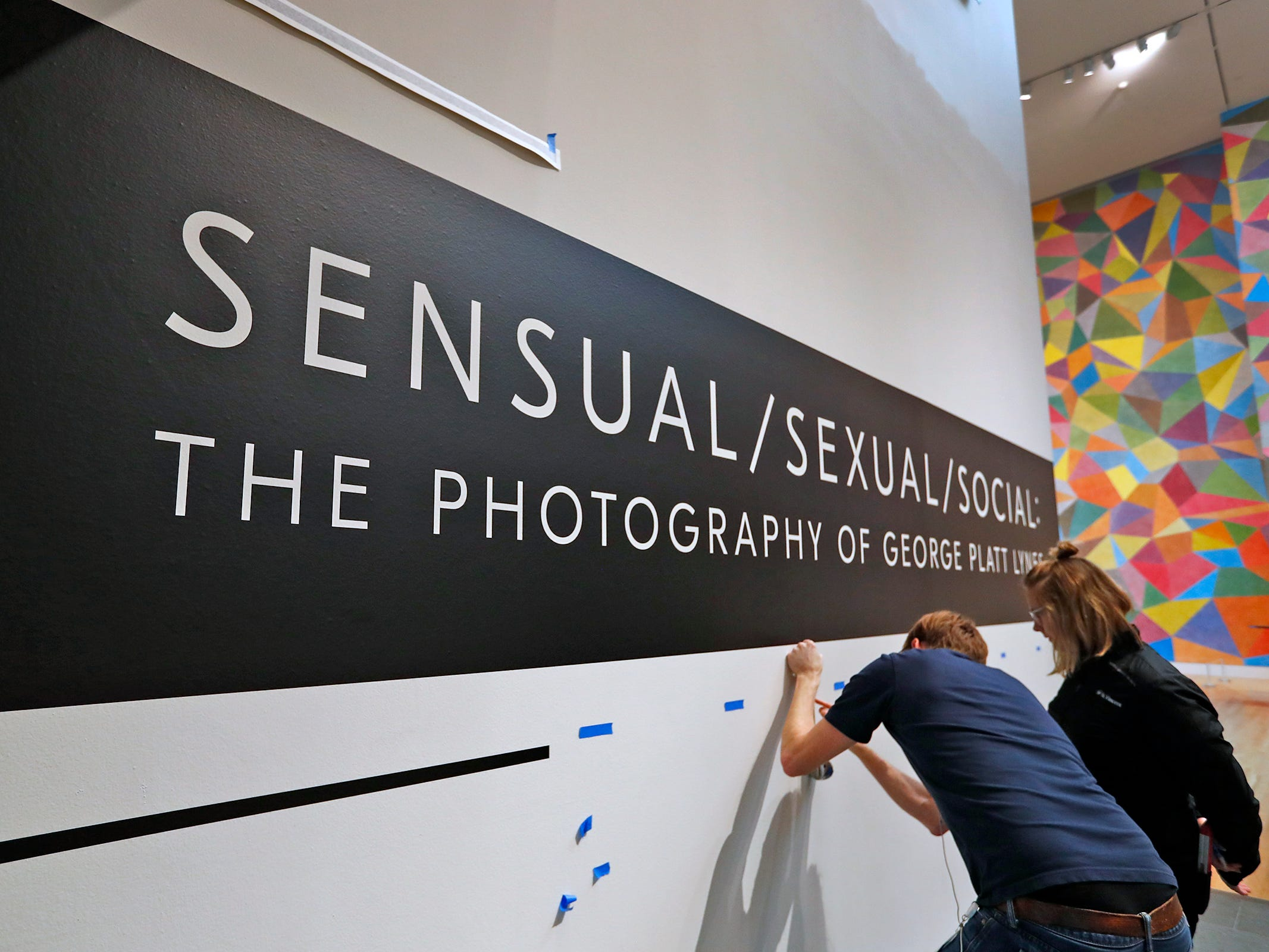 "People put up the signage for the new ""Sensual / Sexual / Social:  The Photography of George Platt Lynes"" exhibit at Newfields, Wednesday, Sept. 26, 2018.  Lynes gained fame as a commercial and ballet photographer in the 1930s and 1940s, but he wanted to be known for the male nudes he captured of the male ballet dancers and others.  The exhibit runs Sept. 30, 2018 through Feb. 24, 2019."